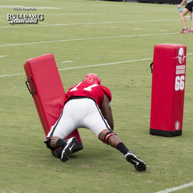 Isaiah Wynn practicing cut block on dummy.