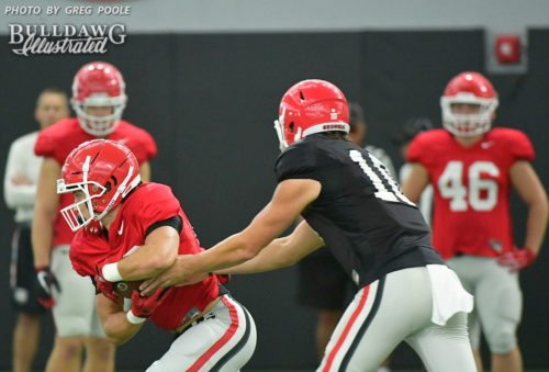 Jacob Eason (10) hands the ball off to one of the running backs