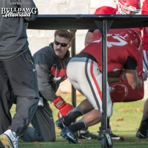 Georgia football team works on a challenging ball security drill under the chute during Wednesday's practice, where Assistant Strength and Conditioning Coach Aaron Fields punches at the ball and the player is also struck by players with blocking pads coming out of the chute while the player has to stay low and maintain his balance.