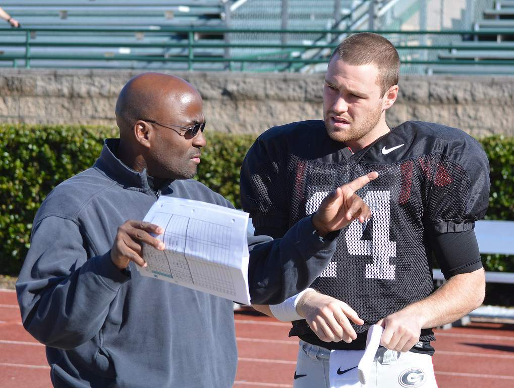 Coach Tony Ball and quarterback Hutson Mason talk during a Belk Bowl practice at Charlotte Country Day School in Charlotte, N.C., on Friday, Dec. 26, 2014. (Photo by Steven Colquitt)