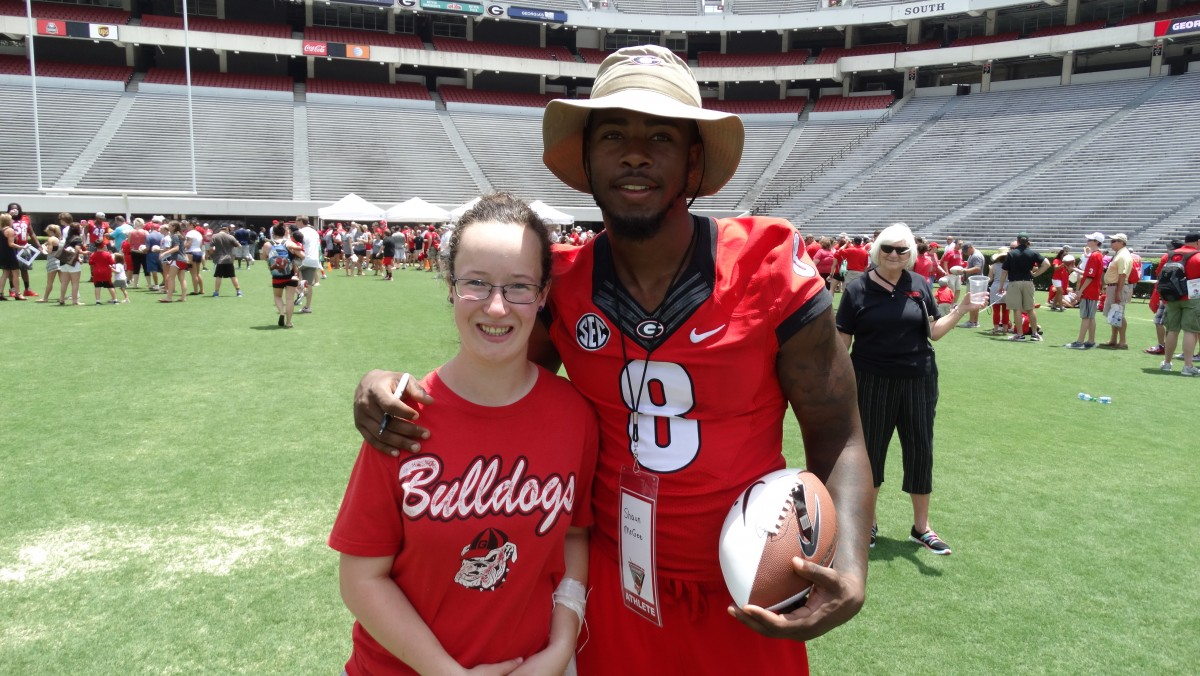 Sophomore OLB Shaun McGee posing with a young Bulldawg Fan. Picture by Greg Poole.