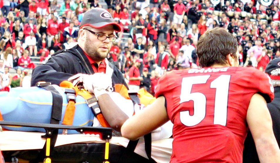 Jake Ganus speaks with injured Southern University player Devon Gales.