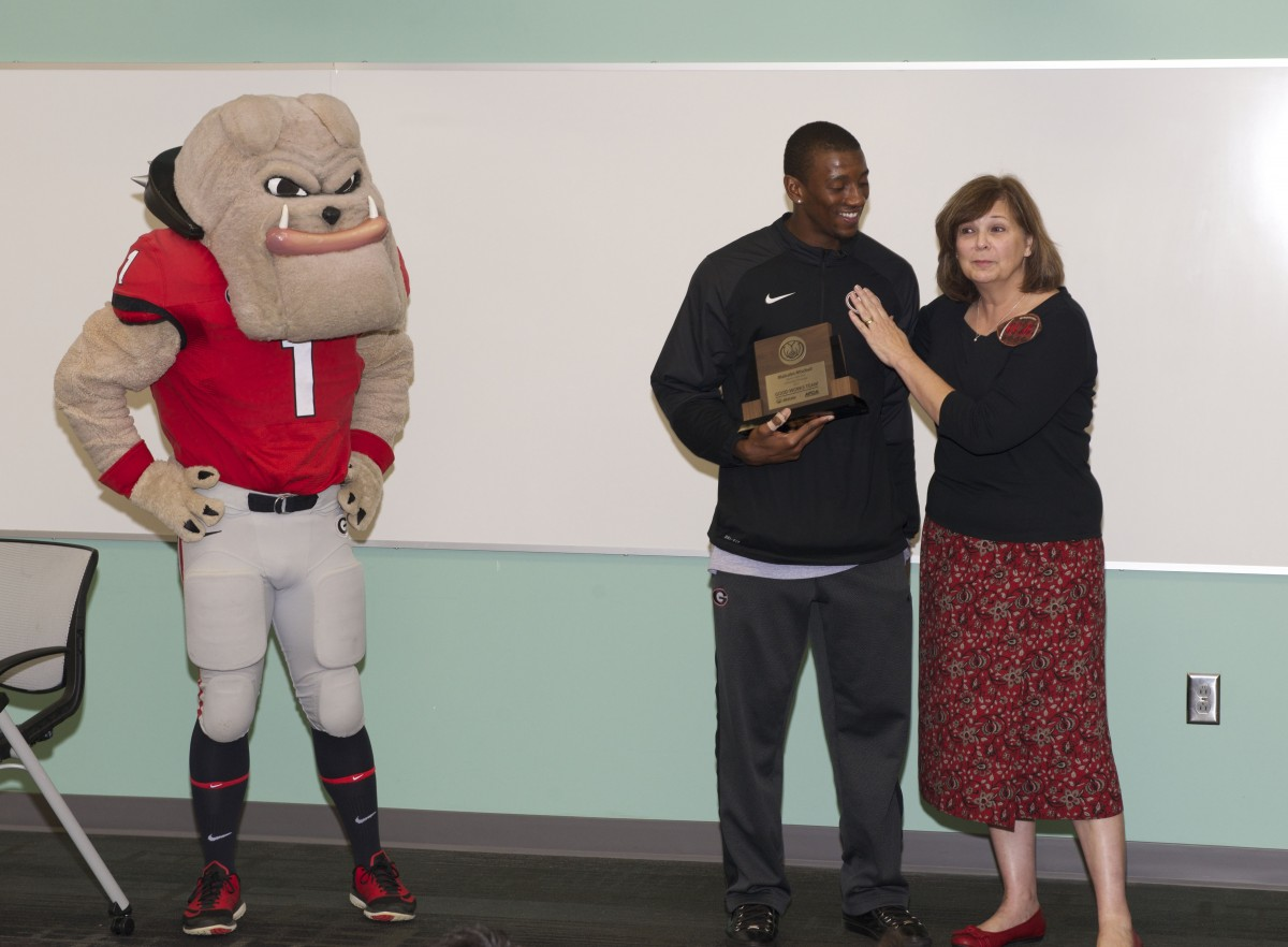 Kathy Rackley, local book club member, congratulates Malcolm Mitchell on receiving his 2015 Allstate AFCA Good Works Team trophy during surprise event at Barrow Elementary School on October 13, 2015.