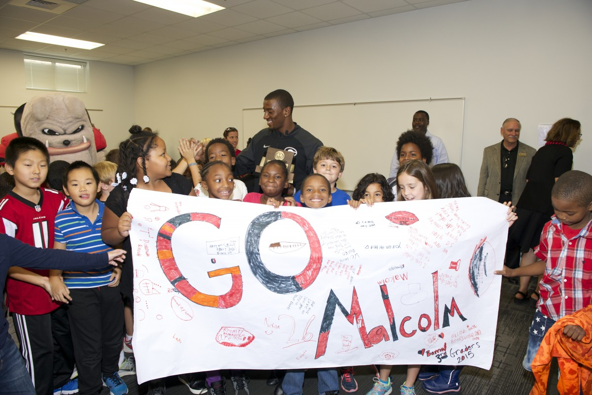 Barrow Elementary School students show off their handmade signs to help congratulate University of Georgia wide receiver, Malcolm Mitchell, after he was surprised with his Allstate AFCA Good Works Team trophy on October 13, 2015.