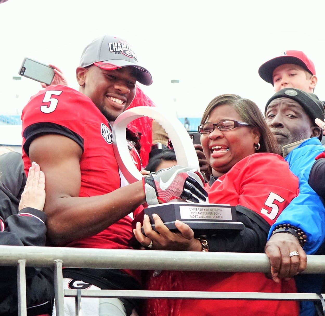 Terry and Mrs. Godwin with MVPs trophy - TaxSlayer Bowl post-game 02-JAN-2016