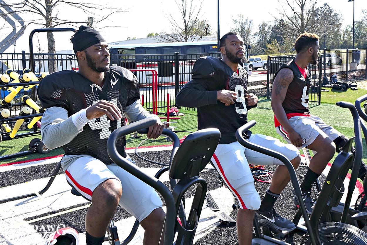 Injured players Chuks Amaechi (41), Reggie Wilkerson (9) and Natrez Patrick (6) work on exercise bikes