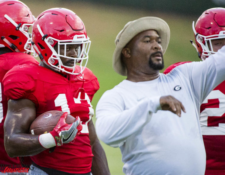 Elijah Holyfield receives instructions from running backs coach Del McGee