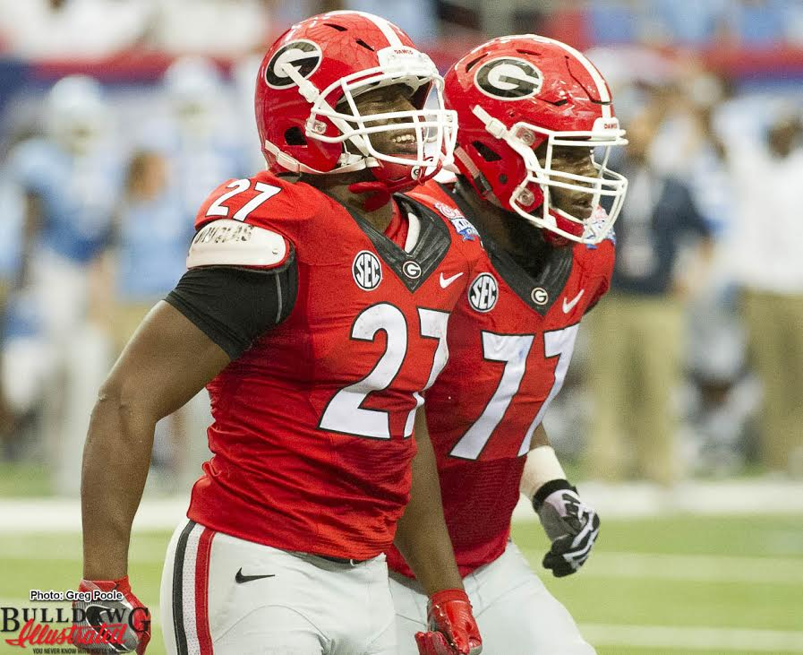 Nick Chubb (27) with a big smile after scoring a TD with Isaiah Wynn (77)
