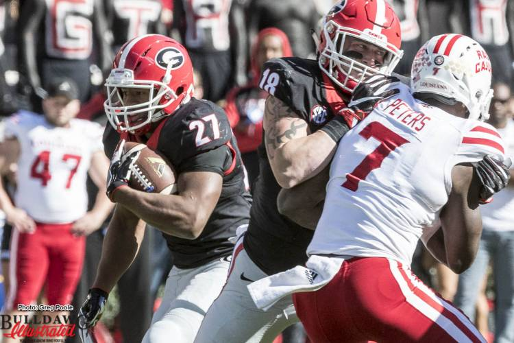 Nick Chubb (27) carrying the ball and Isaac Nauta (18) with the block
