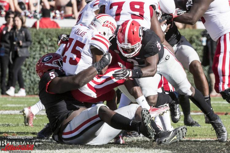 Julian Rochester (5) and Roquan Smith (3) tackle ULL RB Raymond Calais (25)