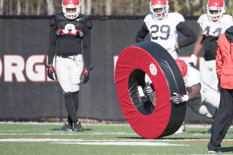 Players go through drill with tackling tube.