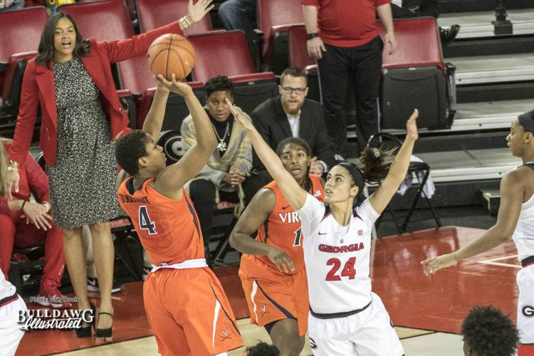 Simone Costa attempts to block a shot as head coach Joni Taylor looks on.