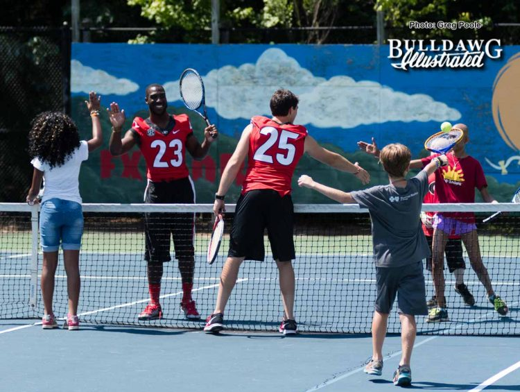 Shakenneth Williams (23) and Steven Van Tiflin (25) shake hands with other players on the tennis court after a game