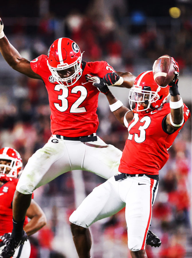 Georgia defensive back Mark Webb (23) celebrates his interception with Georgia inside linebacker Monty Rice (32) during a game against Auburn on Dooley Field at Sanford Stadium in Athens, Ga., on Saturday, Oct. 3, 2020. (Photo by Tony Walsh)
